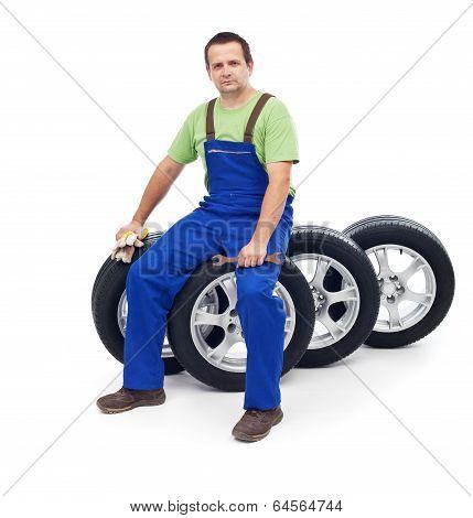 Friendly Car Mechanic Sitting On Tires