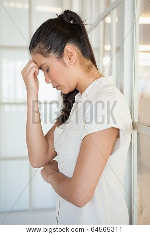 Casual upset businesswoman with head bowed in the office