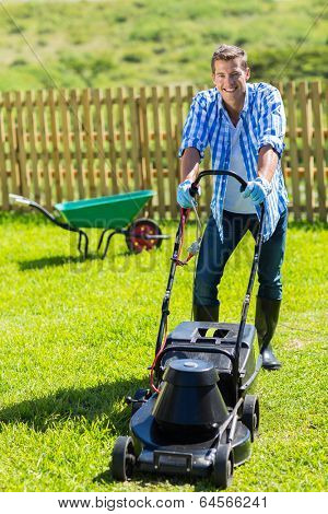 cheerful man lawn mowing in his home garden
