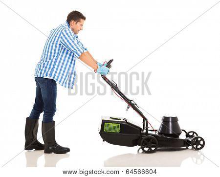 side view of man pushing lawnmower