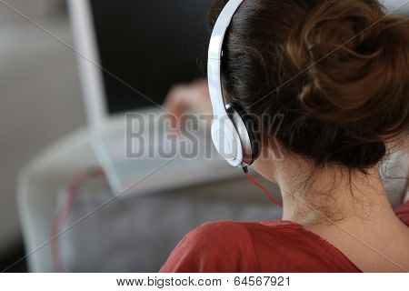 Backview of woman with headphones and laptop