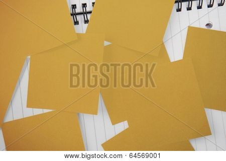 Yellow paper strewn over notepad paper