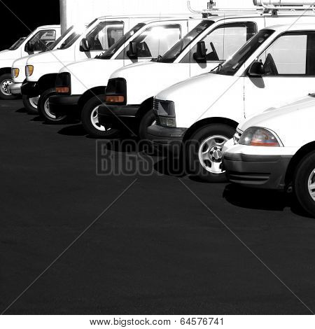 Several cars vans and trucks parked in parking lot for sale