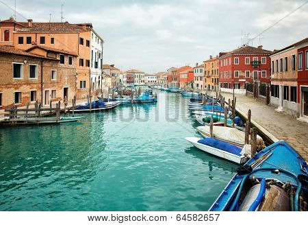 Narrow canal among old colorful houses on island of Murano, near Venice in Italy.