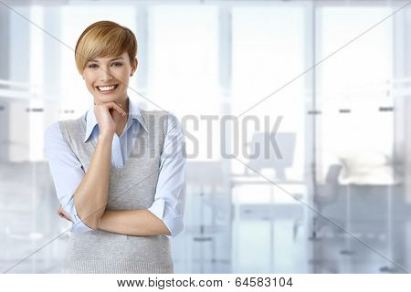 Portrait of happy female office worker at office. Space on right.