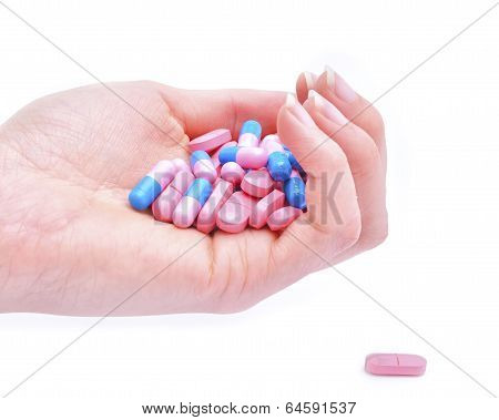 Closeup of a hand holding medications over white