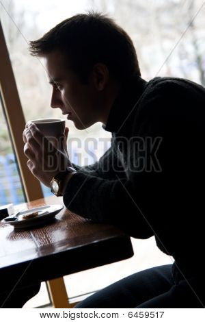 Young Man Drinks Coffee In A Restaurant