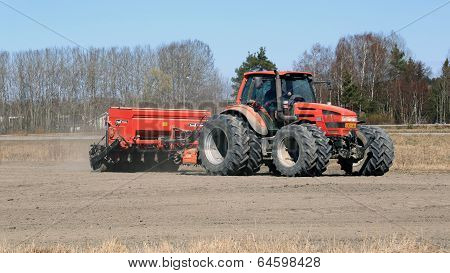 Same Agricultural Tractor And Seeder On Field At Spring