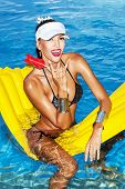 pic of mattress  - Woman with tanned body sitting on yellow air mattress in the pool in summer with lollipop  - JPG