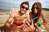 pic of couple sitting beach  - Relaxed young lovers partying on the beach on a sunny day - JPG