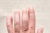 image of braille  - Close up of male hand reading braille text - JPG