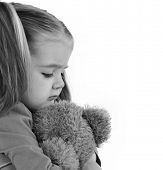foto of love hurts  - A sad little girl is holding a stuffed teddy bear on a white isolated background for a timeout or emotion concept - JPG
