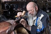 picture of western saddle  - An eighty five year old saddle repairman places artistic embossing on a saddle - JPG