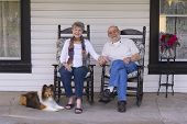 picture of sheltie  - A happy married couple relax on their porch in matching rocking chairs with their Shetland sheepdog by their side - JPG
