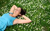 pic of sportive  - Female athlete resting and relaxing after workout. Woman lying down on grass and spring flowers. Healthy lifestyle and happiness concept.