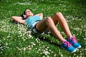 stock photo of rest-in-peace  - Relaxed female runner resting and relaxing after running training. Woman lying down and day dreaming on grass and spring flowers. Healthy lifestyle and happiness concept.