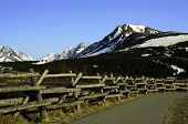 picture of log fence  - A view of a log fence with a walking path and a mountain peak in the distance - JPG