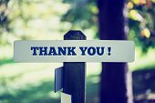 stock photo of thankful  - Thank you signboard on a wooden post in a faded retro image - JPG