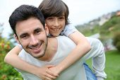 picture of piggyback ride  - Father giving piggyback ride to his son - JPG
