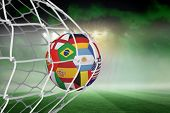 picture of football pitch  - Football in multi national colours at back of net against football pitch under green sky and spotlights - JPG