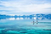 image of paddling  - Two guys paddle boarding calm waters, Lake Tahoe ** Note: Soft Focus at 100%, best at smaller sizes - JPG