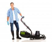 foto of grass-cutter  - good looking man standing next to an electric lawnmower on white background - JPG
