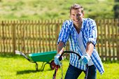 image of grass-cutter  - happy man mowing lawn at home garden - JPG