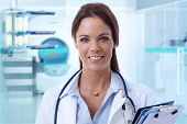 stock photo of mri  - Happy female doctor looking at camera in MRI room of hospital - JPG