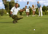 image of flush  - Male golfer and partners happy for successful putt on the green - JPG