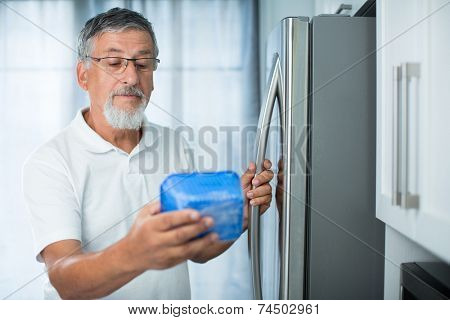 Is this still fine? Senior man in his kitchen by the fridge, looking at the expiry date of a product she took from her fridge -