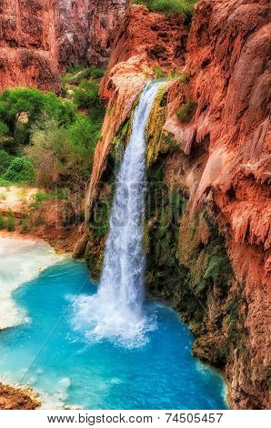 Red rocks of a canyon and falls with blue water.