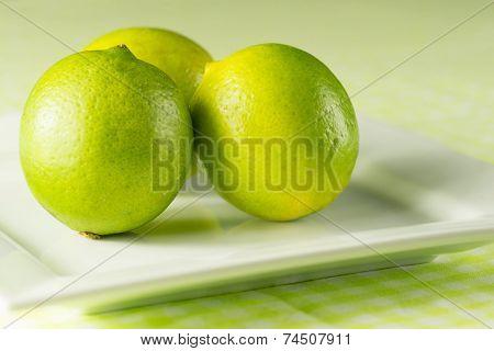Fresh Whole Limes On A Plate