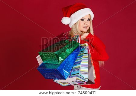 Happy young woman in santa suit carrying shopping bags