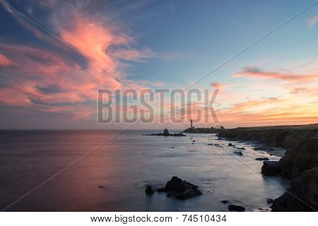 The ocean coast and Lighthouse against the sunset sky.