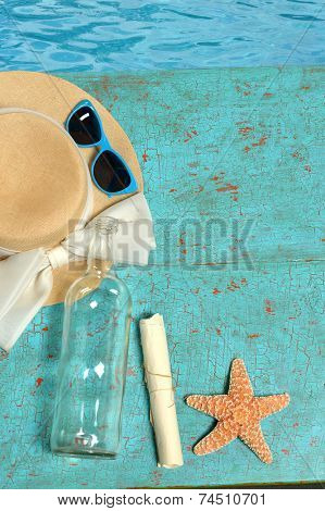 Hat; sunglasses, bottle with message and starfish on painted wood planks