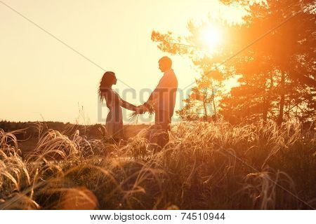 Young couple holding hands at sunrise
