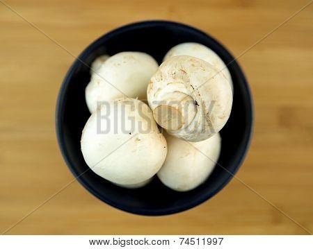 White Mushrooms In Black Bowl On Wooden Board