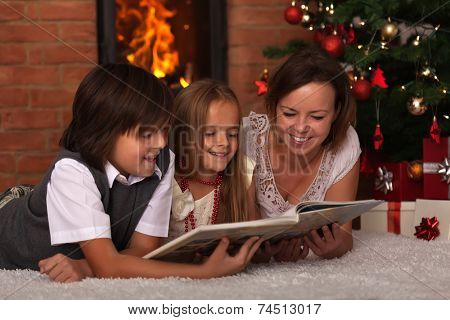 Family reading stories at Christmas time - laying by the fire