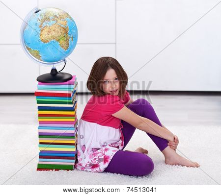 Young student girl with lots to learn - sitting near a book stack