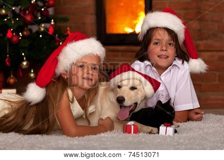 Kids and their pets at Christmas time - laying together at the cozy fire