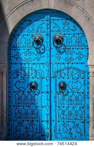 A Blue Door With Black Studs And Stone Ornament At Doorway In Tunisia
