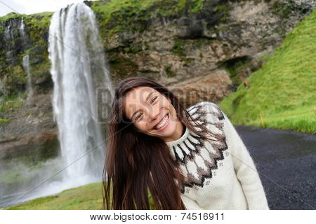 Woman on Iceland in Icelandic sweater by waterfall outdoor fun. Candid beautiful female model in nature landscape with tourist attraction Seljalandsfoss waterfall on Ring Road.