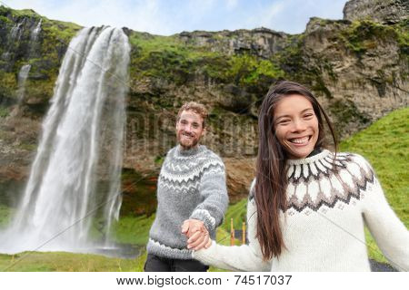 Iceland couple wearing Icelandic sweaters by Seljalandsfoss waterfall on Ring Road in beautiful nature landscape on Iceland. Woman and man model in typical Icelandic sweater. Multiracial couple