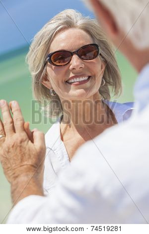 Happy senior woman with perfect teeth dancing with man in a couple and holding hands on a deserted tropical beach with bright clear blue sky