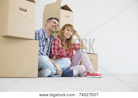 Full-length of happy couple sitting in new house