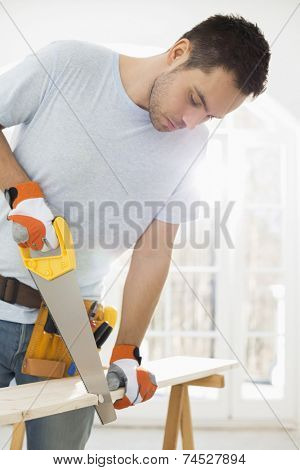 Man sawing wood in new house