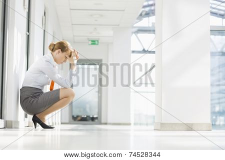Full-length side view of stressed businesswoman crouching at office hallway