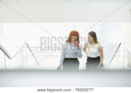Businesswomen having coffee while moving up steps in office