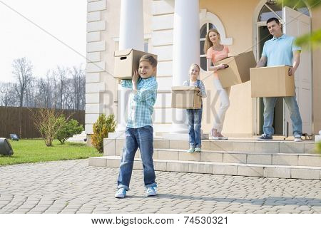 Family with cardboard boxes moving out from house