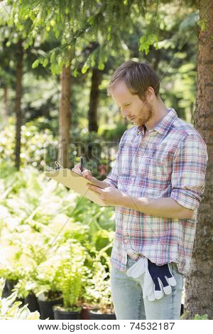 Male supervisor writing on clipboard at plant nursery